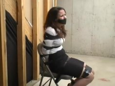 Woman in skirt and heels taped to chair